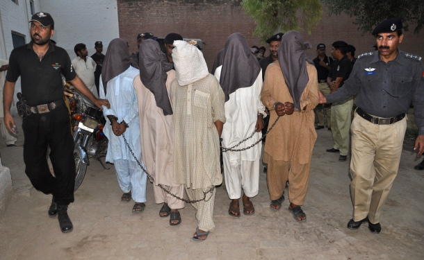 Police escort hooded and detained men to a prison in Bahawalpur